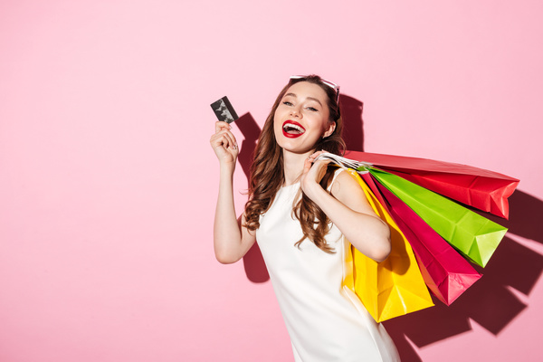 Picture of a cheerful young brunette woman in white summer dress holding credit card posing with shopping bags and looking at camera over pink background.